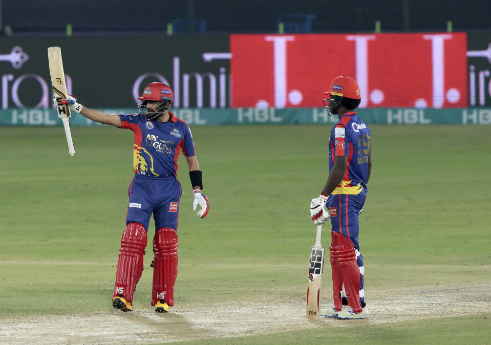 Karachi Kings Babar Azam, left, raises his bat to celebrate his fifty against Lahore Qalandars during the final of their Pakistan Super League T20 cricket match at National Stadium in Karachi, Pakistan, Tuesday, Nov. 17, 2020. (AP Photo/Fareed Khan)