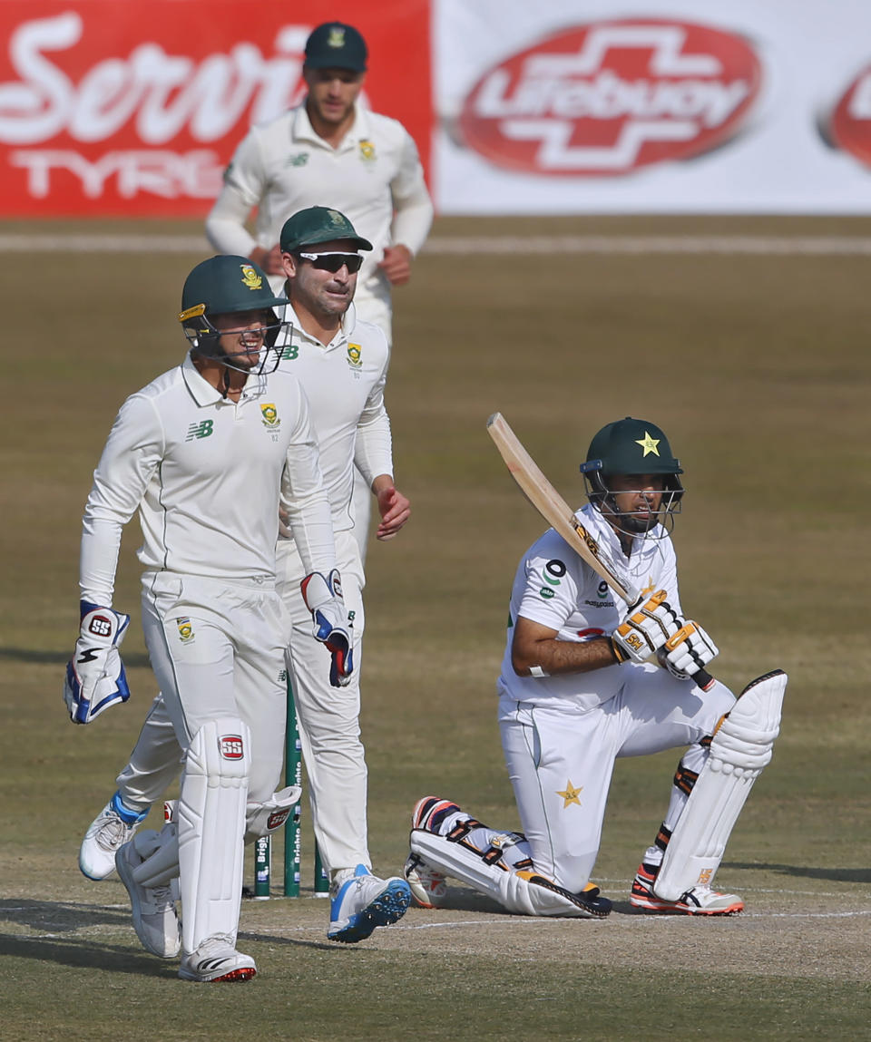 Pakistan's Abid Ali, right, reacts while South Africa's players celebrate his dismissal during the third day of the second cricket test match between Pakistan and South Africa at the Pindi Stadium in Rawalpindi, Pakistan, Saturday, Feb. 6, 2021. (AP Photo/Anjum Naveed)