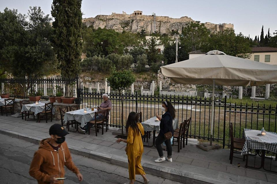 tourists walk past a restaurant overlooking the Roman Agora and the Acropolis hill in Athens