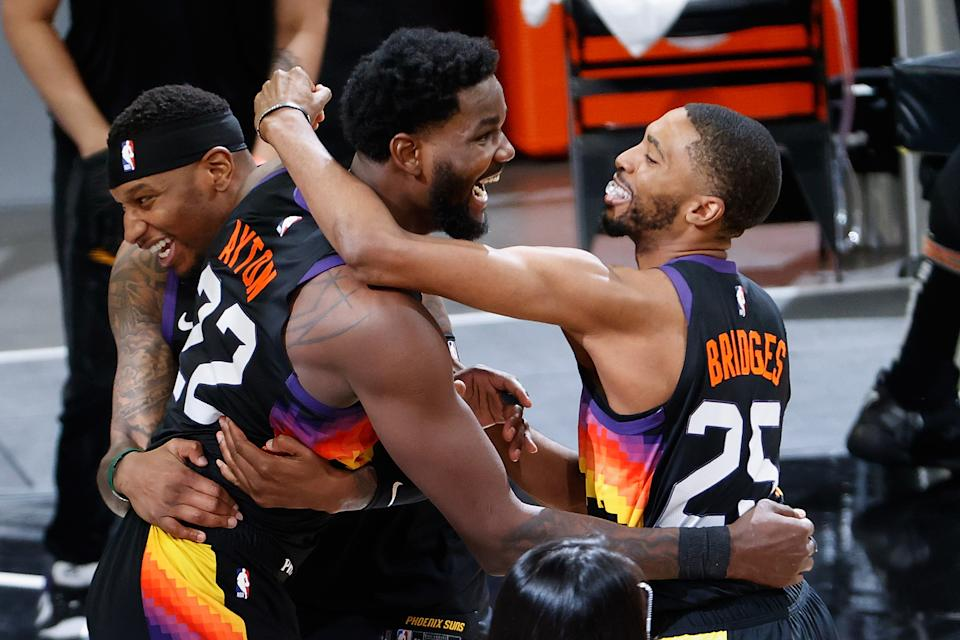 Deandre Ayton (22) Torrey Craig (12) and Mikal Bridges (25) celebrate a Game 2 win, and the Suns will try to clinch a Western Conference title on Monday. (Photo by Christian Petersen/Getty Images)