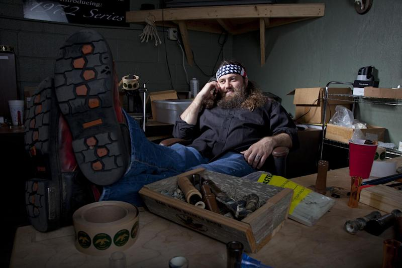 """This undated photo provided by A&E, shows Willie Robertson, star of A&E's """"Duck Dynasty,"""" at his desk in his office at the Duck Commander warehouse in West Monroe, La. Turning small business owners into stars has become a winning formula for television producers, but some businesses featured in them are cashing in, too. Sales explode after just a few episodes air, transforming these nearly unknown small businesses into household names. In addition to earning a salary from starring in the shows, some small business owners are benefiting financially from opening gift shops that sell souvenirs or getting involved in other ventures that spawn from their new-found fame. (AP Photo/A&E)"""