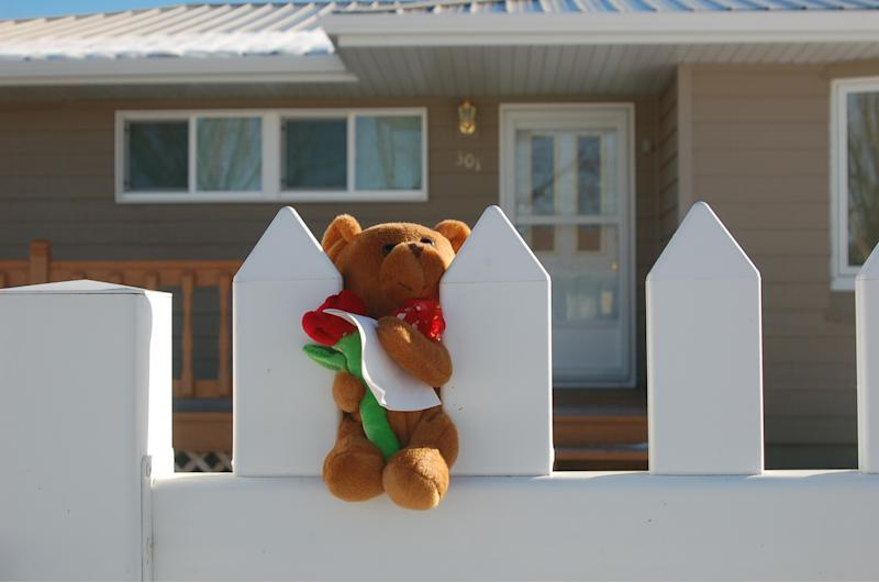A stuffed bear is placed on a white picket fence on Monday, Nov. 19, 2012 in New Town, N.D. Authorities say  a woman and her three grandchildren were murdered in in the home on Sunday, Nov. 18, 2012. Federal investigators are looking at a New Town man who committed suicide in nearby Parshall later Sunday as a person of interest in the case.  (AP Photo/James MacPherson)