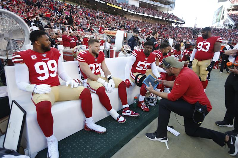 Niners defensive line coach Kris Kocurek talks with DeForest Buckner (99), Nick Bosa (97) and Dee Ford on the sideline during the divisional round. (Photo by Michael Zagaris/San Francisco 49ers/Getty Images)