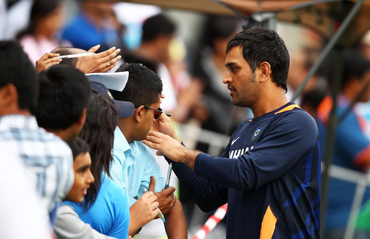 CANBERRA, AUSTRALIA - DECEMBER 19:  MS Dhoni of India sign autographs during a break in play on day one of the International Tour match between India and the Cricket Australia Chairman's XI at Manuka Oval on December 19, 2011 in Canberra, Australia.  (Photo by Mark Nolan/Getty Images)