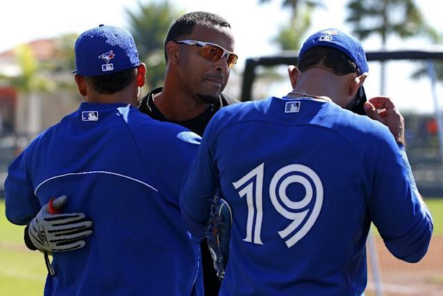 Baltimore Orioles' Nelson Cruz, center, visits with Toronto Blue Jays' Melky Cabrera, left, and Jose Bautista (19) before an exhibition spring training baseball game in Sarasota, Fla., Saturday, March 1, 2014. (AP Photo/Gene J. Puskar)