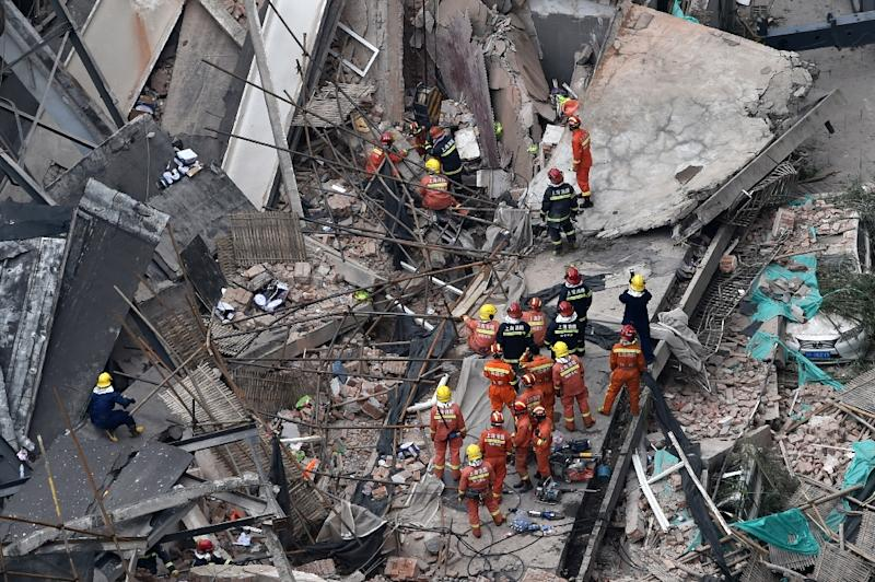 Rescue personnel pulled bloodied and dust-coated workers out from rubble in Shanghai following the roof collapse (AFP Photo/Hector RETAMAL)