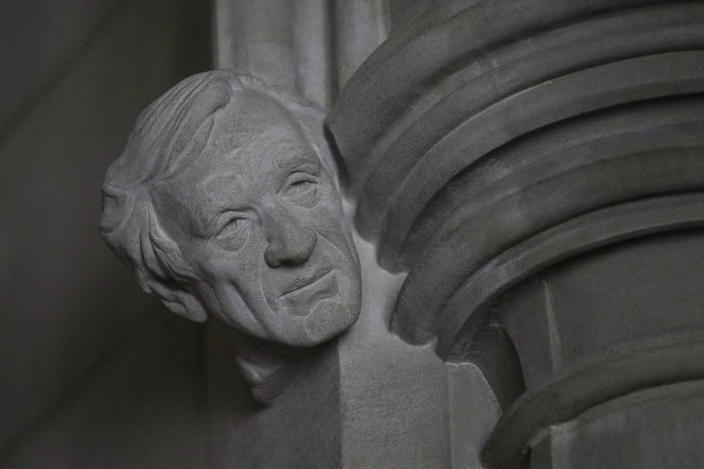 """A limestone head of Holocaust survivor and Nobel Peace Prize winning author Elie Wiesel, carved by Sean Callahan from a clay sculpture by artist Chas Fagan, is almost complete in the Human Rights Porch of the Washington National Cathedral, Friday, April 16, 2021. Wiesel, who died in 2016, was the author of 57 books including """"Night,"""" which is based on his experiences as a Jewish prisoner in the Auschwitz and Buchenwald concentration camps. He became an outspoken advocate for human rights causes around the world, helped found the United States Holocaust Memorial Museum and was awarded the Nobel Peace Prize in 1986. (AP Photo/Carolyn Kaster)"""