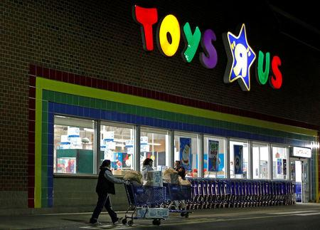 """FILE PHOTO:  Consumers leave a Toys R Us store with full shopping carts after shopping on the day dubbed """"Black Friday"""" in Framingham, Massachusetts, U.S., November 25, 2011.   REUTERS/Adam Hunger/File Photo"""