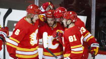 Calgary Flames' Johnny Gaudreau, center, celebrates his goal with teammates during second-period NHL hockey game action against the Vancouver Canucks in Calgary, Alberta, Monday, Jan. 18, 2021. (Jeff McIntosh/The Canadian Press via AP)
