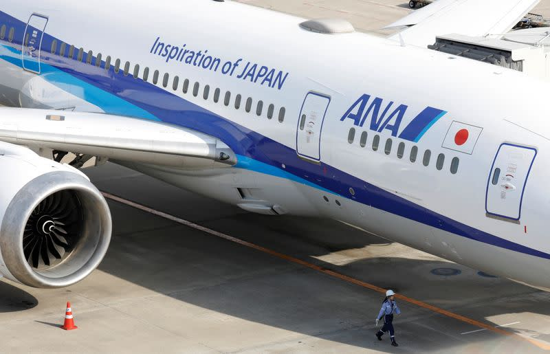 A ground crew member walks next to an All Nippon Airways (ANA) aircraft at the Tokyo International Airport