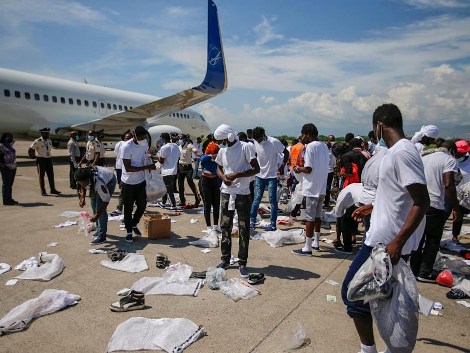 Haitians deported from the United States recover their belongings scattered on the tarmac of the Toussaint Louverture airport in Port-au-Prince, Haiti. (The Associated Press/Joseph Odelyn - image credit)