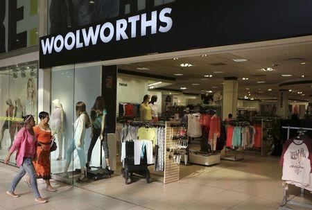 Shoppers walk into a Woolworths store at a shopping center in Lenasia, south of Johannesburg