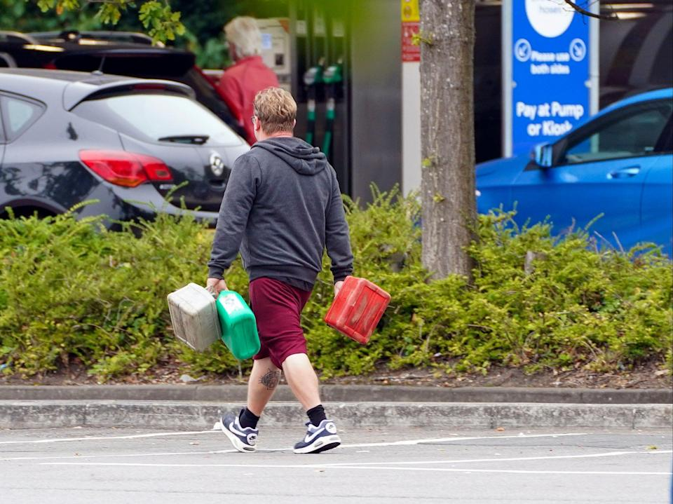 A man carrying multiple fuel containers at a Tesco petrol station in Bracknell, Berkshire (PA)