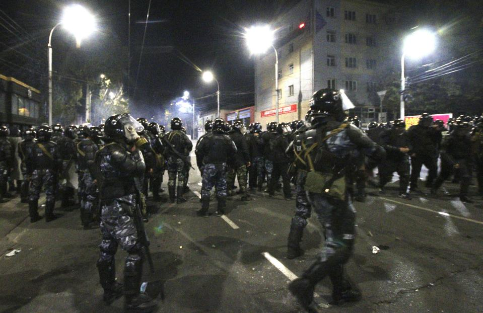 Riot police move to disperse protesters during a rally against the results of a parliamentary vote in Bishkek, Kyrgyzstan, Monday, Oct. 5, 2020. Large crowds of people have gathered in the center of Kyrgyzstan's capital to protest against the results of a parliamentary election, early results of which gave the majority of seats to two parties with ties to the ruling elites amid allegations of vote buying. (AP Photo/Azamat Imanaliyev)