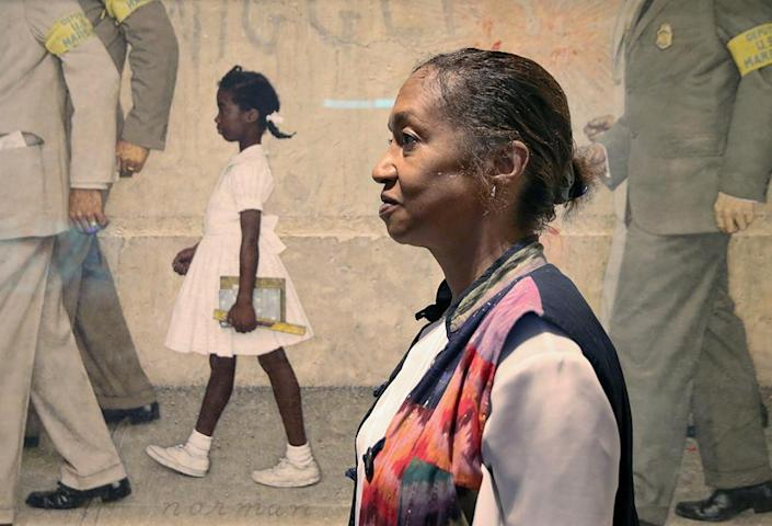 """Lynda Gunn poses next to the 1964 Rockwell painting """"The Problem We All Live With"""" during the Norman Rockwell Museum's models reunion day in Stockbridge, Mass., on July 16, 2016. Gunn modeled as Ruby Bridges in the painting, which depicts the 1960 fight over school desegregation in New Orleans. (Timothy Tai for The Boston Globe via Getty Images)"""