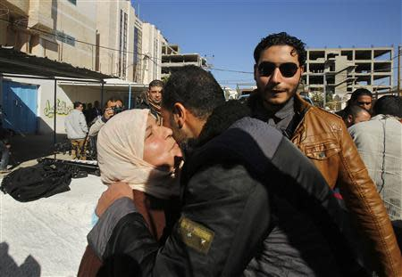 A Palestinian woman hugs her son upon his release from a Hamas-run jail in Gaza City January 8, 2014. REUTERS/Suhaib Salem