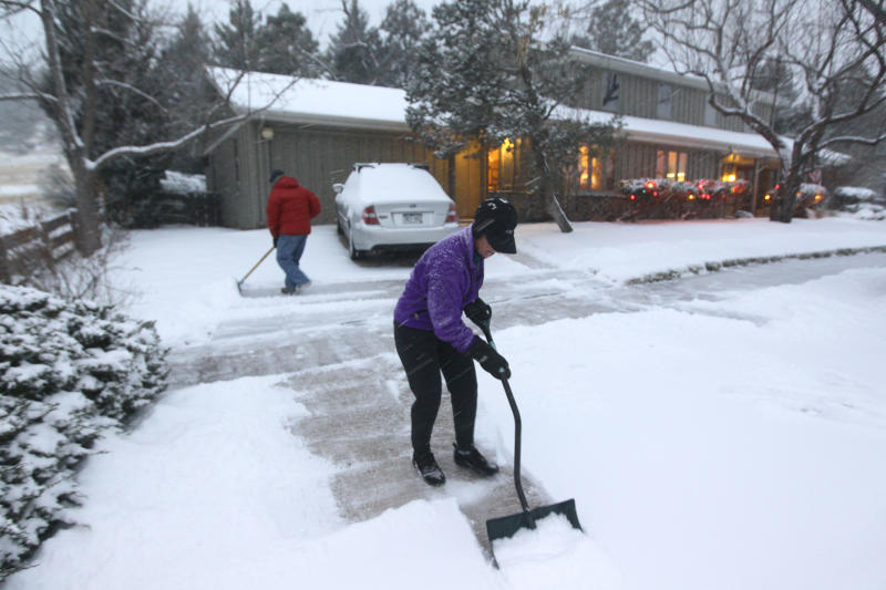 A woman and her husband shovel their walk as a blizzard dropped snow over Boulder, Colo., Wednesday Dec. 19, 2012. A storm that has dumped more than a foot of snow in the Rocky Mountains is heading east and is forecast to bring the first major winter storm of the season to the central plains and Midwest. (AP Photo/Brennan Linsley)