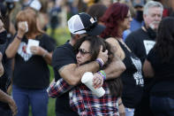 Jimmy Long, left, embraces Debby Allen, mother of victim Christopher Roybal, during a ceremony Thursday, Oct. 1, 2020, on the anniversary of the mass shooting three years earlier in Las Vegas. The ceremony was held for survivors and victim's families of the deadliest mass shooting in modern U.S. history. (AP Photo/John Locher)