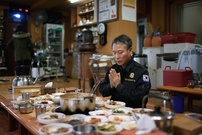 Kim Ki-Ho, head of the Korea Research Institute for Mine Clearance, prays prior to a meal at a restaurant near the Demilitarized Zone in Yeoncheon, South Korea (AFP Photo/Ed Jones)