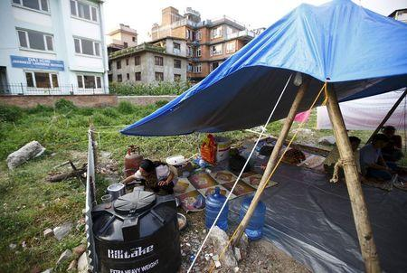Mira Bajracharya, a lesbian, cooks inside a temporary makeshift shelter at a lesbian, gay, bisexual and transgender (LGBT) camp, a month after the April 25 earthquake in Kathmandu, Nepal