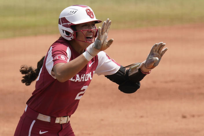 Oklahoma's Tiare Jennings celebrates as she runs toward home plate with a home run against James Madison in the first inning of an NCAA Women's College World Series softball game Sunday, June 6, 2021, in Oklahoma City. (AP Photo/Sue Ogrocki)