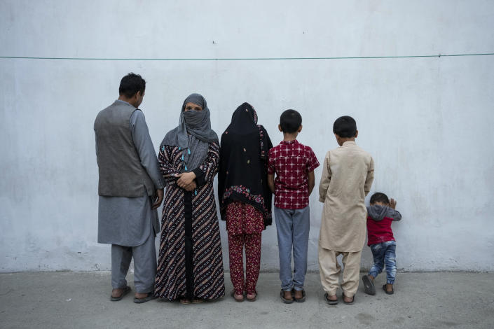 """Najia, second left, pose with her family in Kabul, Afghanistan, Friday, Oct. 1, 2021. Soon after the Taliban took control of Kabul, the family sold their households and used the money to unsuccessfully cross into Pakistan. Najia, once a bacha posh, believes there is no place for them under the current regime. Bacha posh means in Dari """"dressed up as a boy"""" and is a regional tradition that allowed parents to dress and raise their daughters as boys with the goal to provide them with a different life. (AP Photo/Bernat Armangue)"""