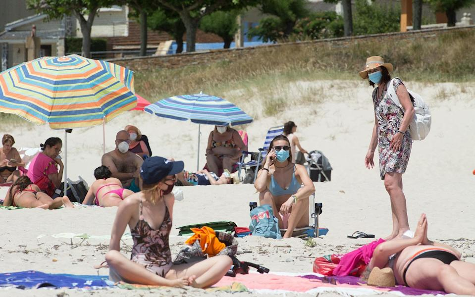 Sunbathers wear face masks on a beach in Galicia - Getty