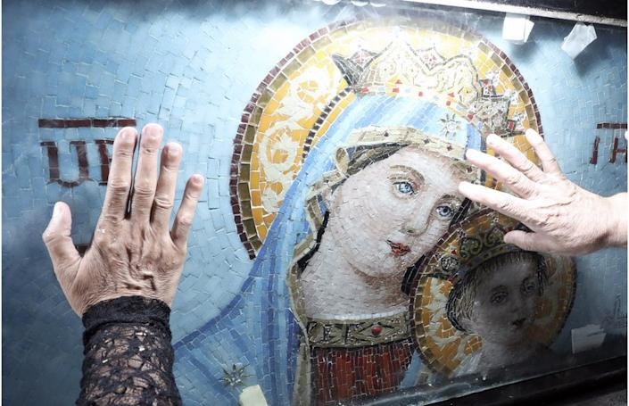 Coptic Christians touch a mosaic of the Virgin Mary soon after Egypt's churches reopened on Monday