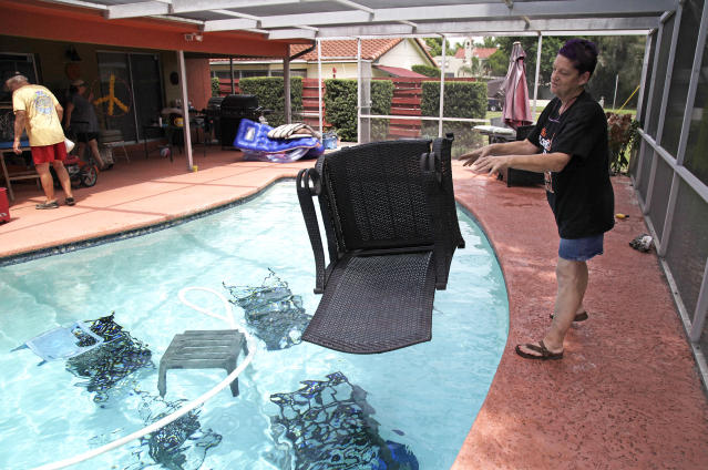 <p>Jackie Kreuter, 56, of Gulfport, Fla., tosses pool furniture in the pool Tuesday, Sept. 5, 2017 so it doesn't fly around during the impending hurricane. Kreuter, along with her mother, husband, sister, daughter, grandson, five dogs and a bird are boarding up their home and business and leaving for Ocala to get out of Hurricane Irma's way. (Photo: Lara Cerri/The Tampa Bay Times via AP) </p>