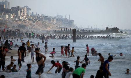 Palestinians swim to cool off in the Mediterranean Sea off the coast of the northern Gaza Strip July 13, 2018.  REUTERS/Mohammed Salem