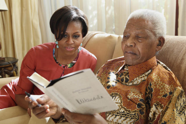 In this photo provided by the Nelson Mandela Foundation on Tuesday, June 21, 2011, US First Lady Michelle Obama, left, with former South African President Nelson Mandela, at this home, in Houghton, South Africa. First lady Michelle Obama and her family met with Nelson Mandela during a private visit at the former South African president's home. Mrs. Obama, daughters Malia and Sasha, and her mother, Marian Robinson, were viewing some of Mandela's personal papers at his foundation Tuesday when according to White House officials, he sent word that he wanted to meet them. It was Mrs. Obama's first meeting with the prisoner-turned-president. (AP Photo/ Debbie Yazbek, Nelson Mandela Foundation)