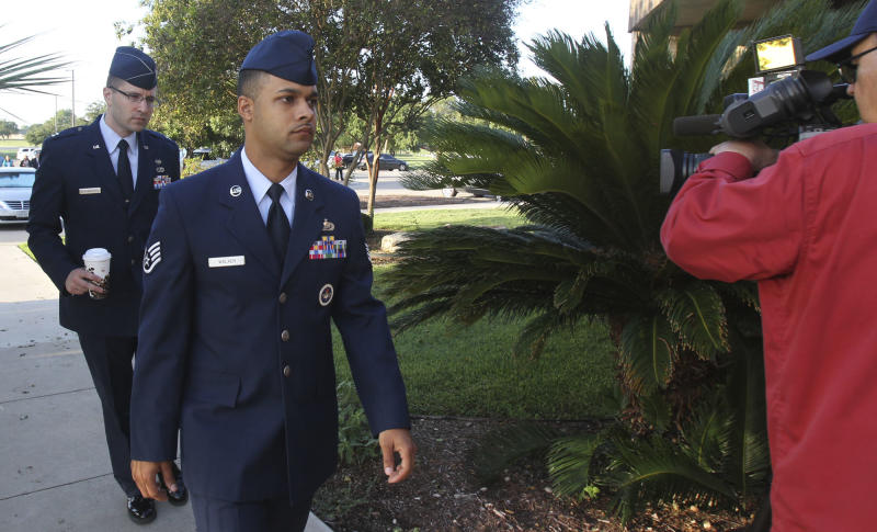 Air Force Staff Sgt. Luis Walker, left foreground, arrives for the fourth day of his trial at Lackland Air Force Base in San Antonio, Texas, Friday, July 20, 2012. Walker is accused of sexually assaulting 10 basic trainees, with charges ranging from rape and aggravated sexual assault to obstructing justice and violating rules of professional conduct. If convicted, he could be sentenced to life imprisonment. (AP Photo/San Antonio Express News, Billy Calzada)