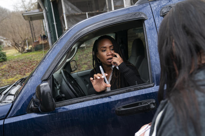 Larrecsa Cox, who leads the Quick Response Team, demonstrates to Yvonne Ash outside her home in Branchland, W.Va., Monday, March 15, 2021, how to administer the overdose reversal medication naloxone, just days after her son overdosed. Ash found her 33-year-old son, Steven, slumped among the piles of used tires behind the shop his family has owned for generations. Pleading and crying, she had thrown water on him because she couldn't think of anything else to do. (AP Photo/David Goldman)
