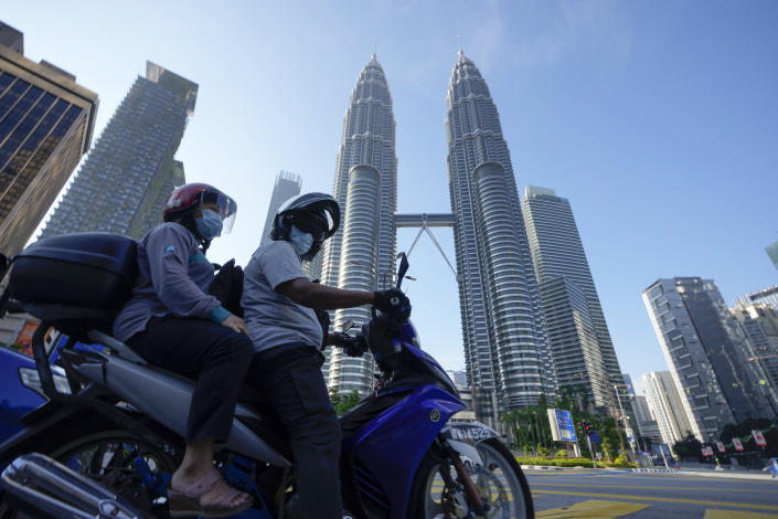 Motorists wearing face masks wait in front of the Twin Towers during the first day of Full Movement Control Order (MCO) in Kuala Lumpur, Malaysia, Tuesday, June 1, 2021. Malls and most businesses in Malaysia shuttered Tuesday as the country began its second near total coronavirus lockdown to tackle a worsening pandemic that has put its healthcare system on the verge of collapse. (AP Photo/Vincent Thian)