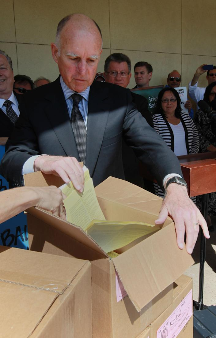 Gov. Jerry Brown looks through a box of petitions for his tax-hike initiative before submitting them to the Sacramento County Registrar of Voters in Sacramento, Calif., Thursday, May 10, 2012. Brown's initiative is one of two tax hike petitions that are expected to qualify for November ballot. Brown has warned that if voters do not pass the tax hikes there would be even deeper cuts to schools, higher education and social services. (AP Photo/Rich Pedroncelli)