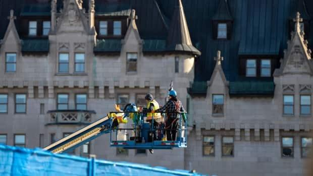 Construction workers are moved into place near Parliament Hill's East Block earlier this week.  (Andrew Lee/CBC - image credit)