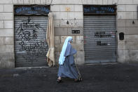 FILE - In this March 15, 2021, file photo, a nun wearing a face mask to curb the spread of COVID-19, walks past a closed shop in downtown Rome. Lofty hopes that the crisis would encourage a new and tighter bloc to face a common challenge have given way to the reality of division: The pandemic has set member nation against member nation, and many capitals against the EU itself, as symbolized by the disjointed, virtual meetings leaders now hold. In Italy, Premier Giuseppe Conte was forced to resign over his handling of the economic fallout of the pandemic. (AP Photo/Alessandra Tarantino, File)