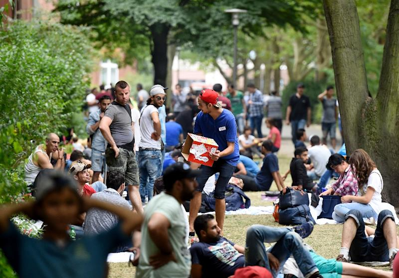 Refugees wait outside the State Office of Health and Social Affairs Berlin to receive help from authorities on August 7, 2015, as the country braces to host a record 800,000 asylum seekers (AFP Photo/Tobias Schwarz)