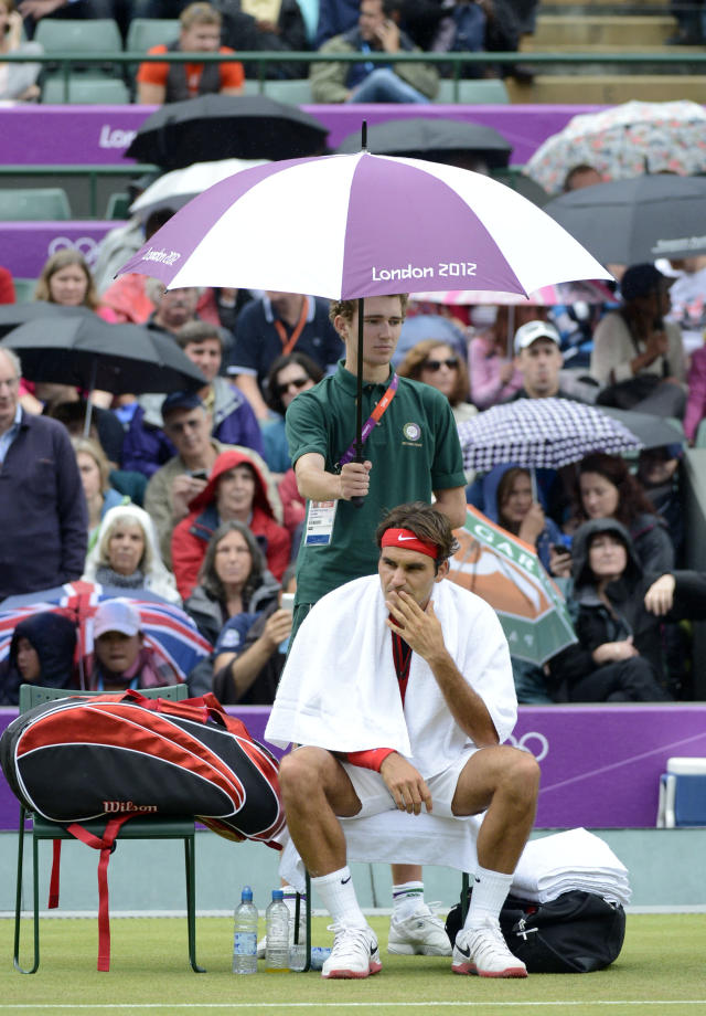 Aug 1, 2012; London, United Kingdom; Roger Federer (SUI) sits under an umbrella as rain delays his match against Denis Istomin (UZB) in the third round of men's tennis during the London 2012 Olympic Games at Basketball Arena. Mandatory Credit: Richard Mackson-USA TODAY Sports