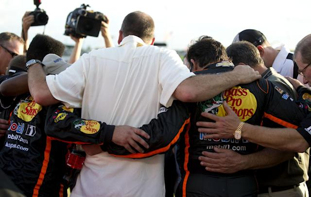 Sprint Cup Series driver Tony Stewart, right, and his crew huddle in prayer before the start of an NASCAR Sprint Cup auto race at Atlanta Motor Speedway Sunday, Aug. 31, 2014, in Hampton, Ga. Stewart was racing for the first tim since he was involved in a fatal dirt track accident in N.Y. (AP Photo/Brynn Anderson)