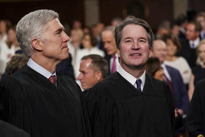 FILE - In this Feb. 5, 2019 file photo, Supreme Court Associate Justices Neil Gorsuch, left, and Brett Kavanaugh watch as President Donald Trump arrives to give his State of the Union address to a joint session on Congress at the Capitol in Washington. President Donald Trump's deep imprint on the federal courts is a rare point of agreement about the president across the political spectrum. With a major assist from Senate Majority Leader Mitch McConnell, Trump and his White House staff relentlessly, almost robotically, filled nearly every opening in the federal judiciary, undeterred by Democratic criticism. (Doug Mills/The New York Times via AP, Pool, File)