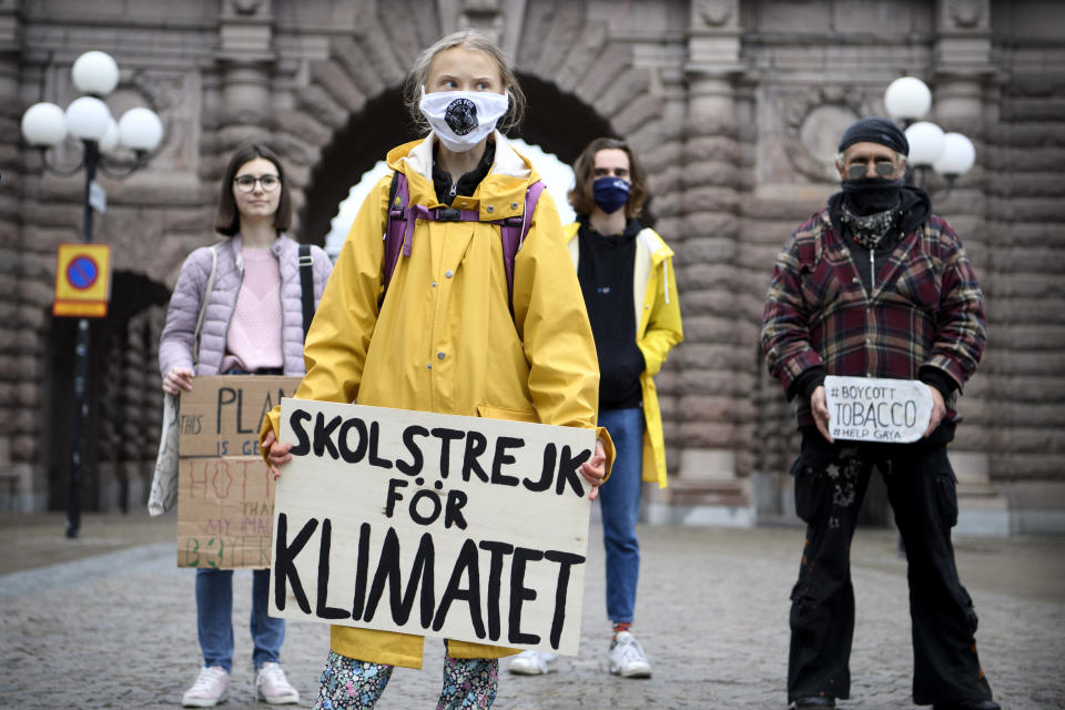 """Swedish climate activist Greta Thunberg, foreground center, holds a sign with writing reading in Swedish """"School Strike for Climate"""" as attends a Fridays For Future protest outside the Swedish Parliament, in Stockholm, Sweden, Friday, Oct. 9, 2020. The winner of this year's Nobel Peace Prize will be announced Friday at 11 a.m. (0900 GMT) in Oslo, with no shortage of causes or candidates on this year's list. Guesses — and bets — this year have focused on Swedish climate activist Greta Thunberg amongst others. (Jessica Gow/TT via AP)"""