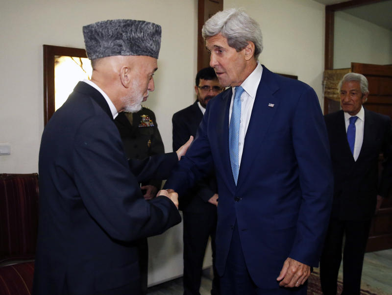 US Secretary of State Kerry (R) is greeted by Afghanistan's President Hamid Karzai (L) in Kabul, on July 11, 2014