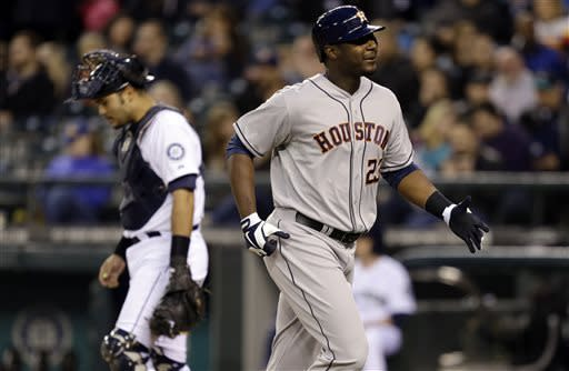 Houston Astros' Chris Carter, right, heads to the dugout past Seattle Mariners catcher Jesus Montero, left, after hitting a home run in the second inning of a baseball game, Tuesday, April 9, 2013, in Seattle. (AP Photo/Ted S. Warren)