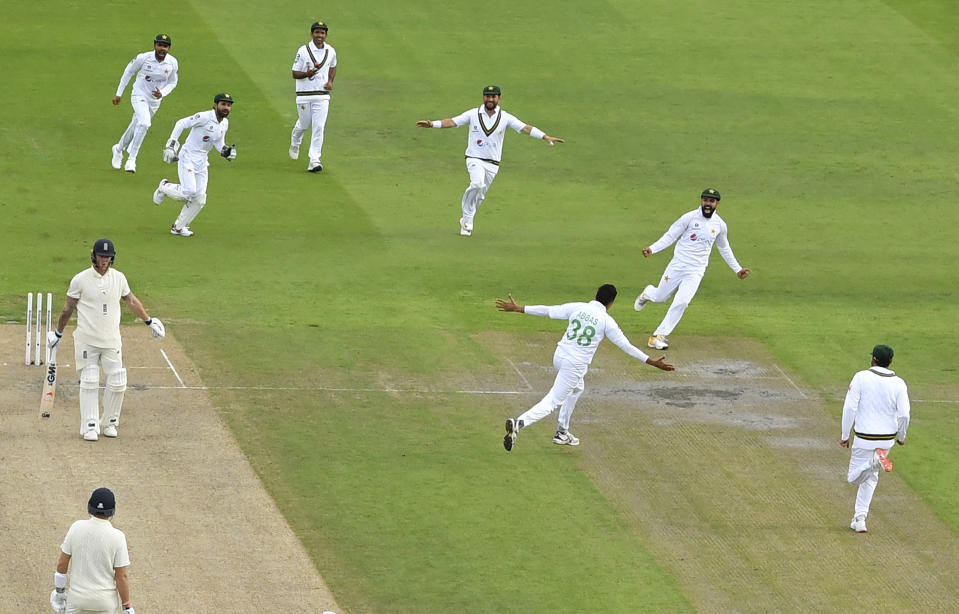 Pakistan's Mohammad Abbas, third right, and teammates celebrate the dismissal of England's Ben Stokes, left, during the second day of the first cricket Test match between England and Pakistan at Old Trafford in Manchester, England, Thursday, Aug. 6, 2020. (Dan Mullan/Pool via AP)