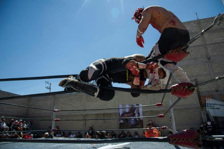 Mexican wrestlers engage in an extreme version of 'lucha libre' in a backyard bout in tribute to wrestler Ovett, who died of Covid-19