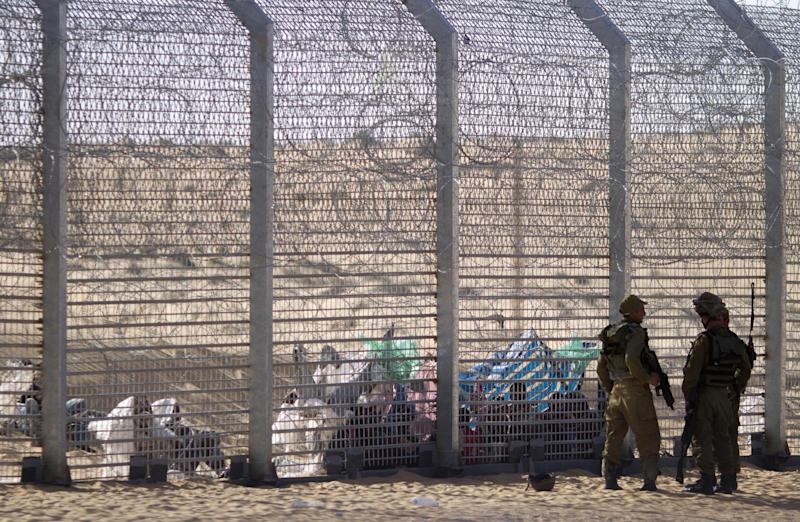 FILE - In this Tuesday, Sept. 4, 2012 file photo, African refugees sit on the ground behind a border fence after they attempted to cross illegally from Egypt into Israel as Israeli soldiers stand guard near the border with Egypt, in southern Israel. Hundreds of African migrants are languishing in a secretive desert detention center in southern Israel, where families may only meet once a week and where women and children sleep in a prison-like compound, according to witnesses who paid a rare visit to the site. (AP Photo/Ariel Schalit, File)