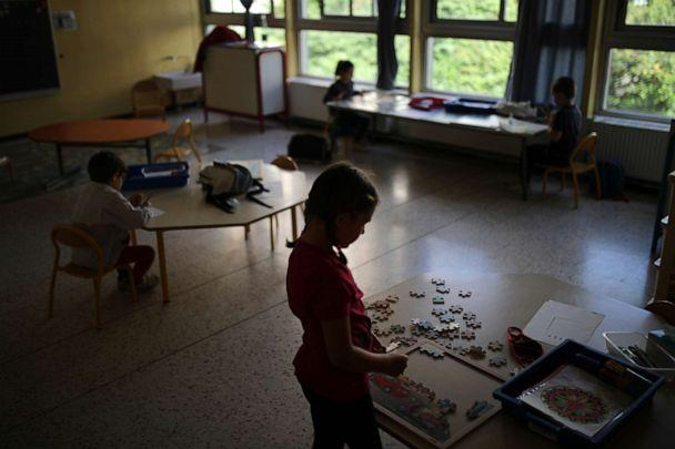 PHOTO: Children respecting social distance play with jigsaw puzzles in a classroom of the Saint-Tronc Castelroc primary school in Marseille, southern France, on May 14, 2020. (Daniel Cole/AP)