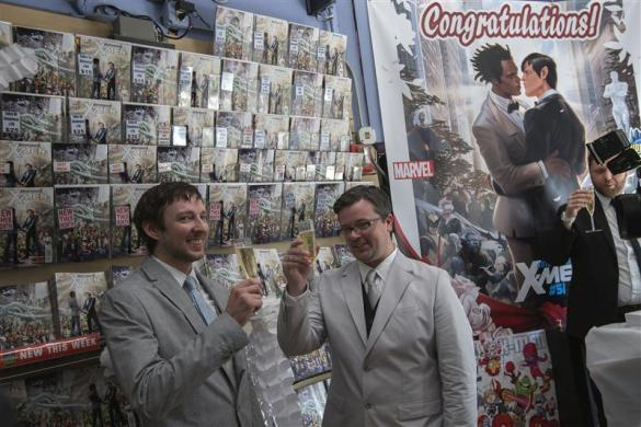 Jason Welker (L) and Scott Everhart raise their glasses in a toast after exchanging vows during their wedding ceremony at a comic book retail shop in Manhattan, New York June 20, 2012.
