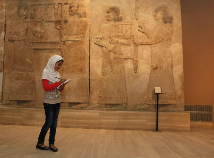 FILE - In this Tuesday, April 2, 2013 file photo, a school student visits the restored Iraqi National Museum in Baghdad, Iraq. Ten years after Iraq's national museum was looted and smashed by frenzied thieves during the U.S.-led invasion in 2003 to topple Saddam Hussein, it's still far from ready for a public re-opening. Work to overcome decades of neglect and the destruction of war has been hindered by power struggles, poorly-skilled staff and the persistent violence plaguing the country, said Bahaa Mayah, Iraq's most senior antiquities official. (AP Photo/Hadi Mizban, File)